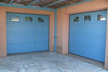 Porte de garage sectionnelle bleue avec portillon installé par Komilfo près de Perpignan